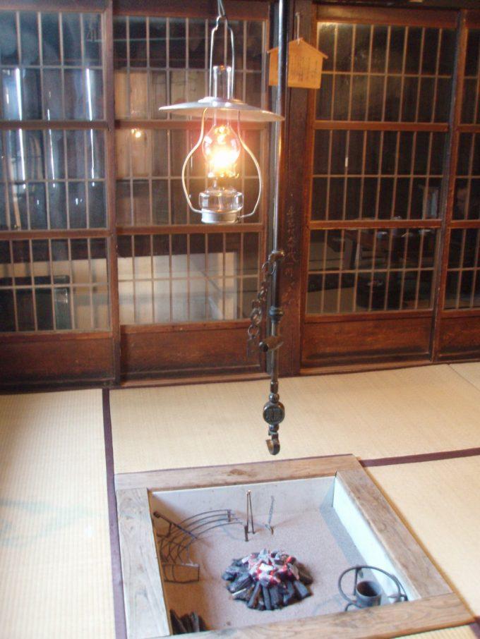 鶴の湯本陣ランプに灯る火と囲炉裏にくべられた炭