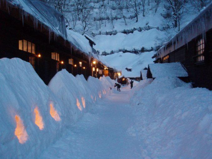暮れ始めの鶴の湯雪壁とろうそくの灯り
