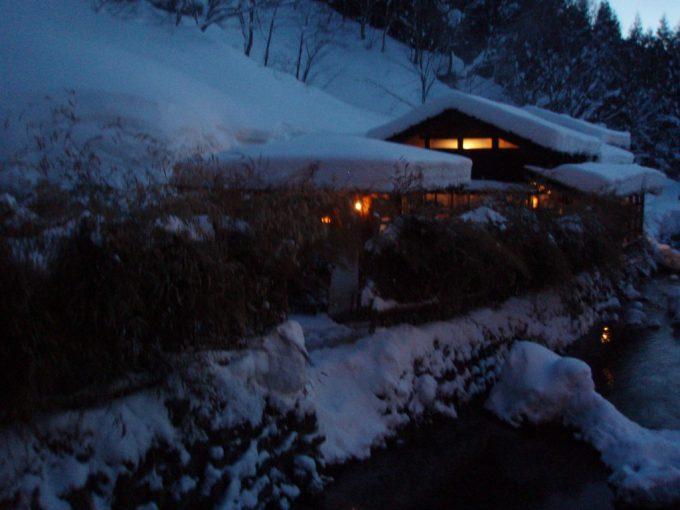 夕闇の鶴の湯灯りがもれる湯屋