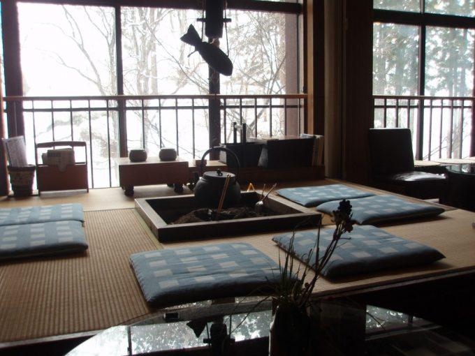 自在館ロビーのいろりと雪景色