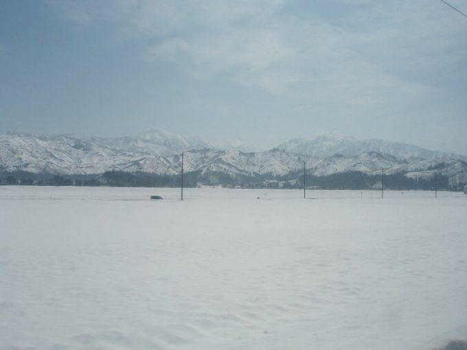春の雪原と白い山なみ
