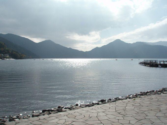 雲間から覗く太陽で照らされた中禅寺湖