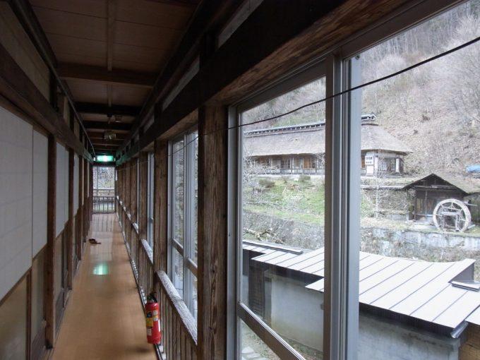 大沢温泉自炊部中舘1階廊下から眺める菊水館茅葺屋根と水車
