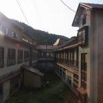 西日に照らされ独特の雰囲気を放つ鉛温泉藤三旅館自炊部の建物と中庭