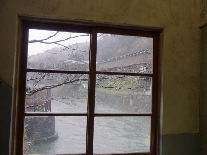 岩手花巻南温泉峡大沢温泉木枠のサッシと雨にけむる茅葺屋根