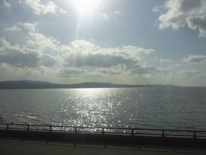 太陽に照らされ輝く宍道湖が広がる一畑電車の車窓
