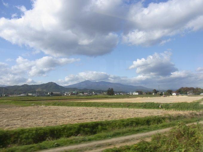 東北本線車窓から眺める秋の田んぼと安達太良山