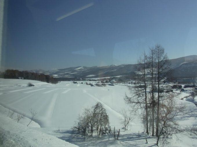 由布の函館本線雪原と羊蹄山の車窓
