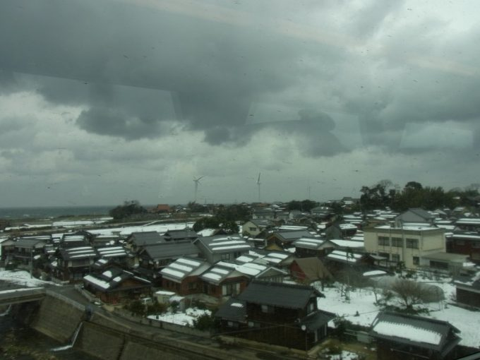 灰色の雲が垂れ込める冬の山陰の家並み