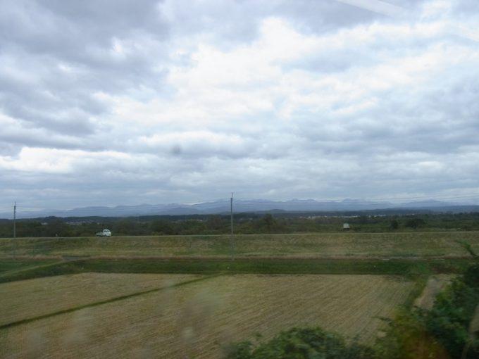 刈り取った秋の田んぼと白神山地