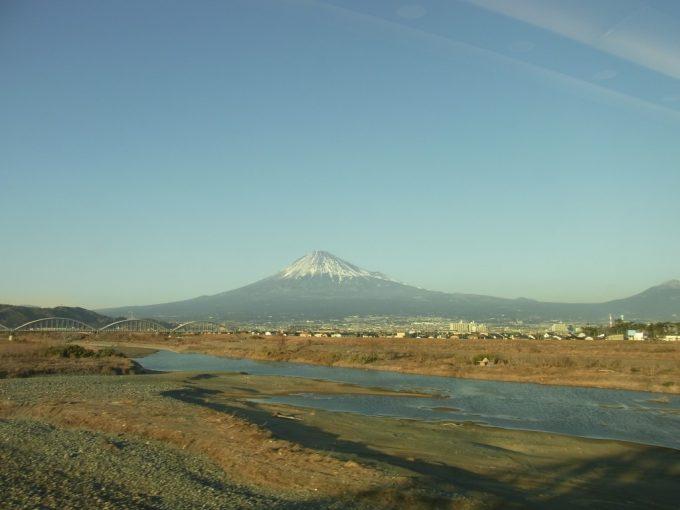 東海道新幹線車窓大井川越しに眺める冬の霊峰富士山