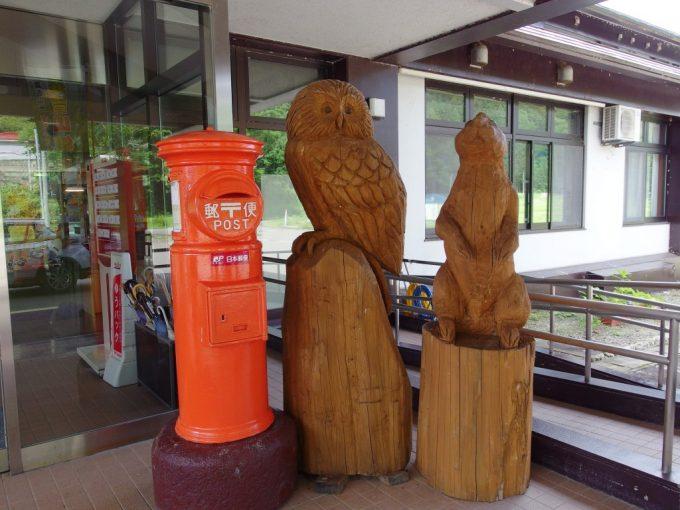 打当温泉マタギの湯玄関の彫刻と赤いポスト