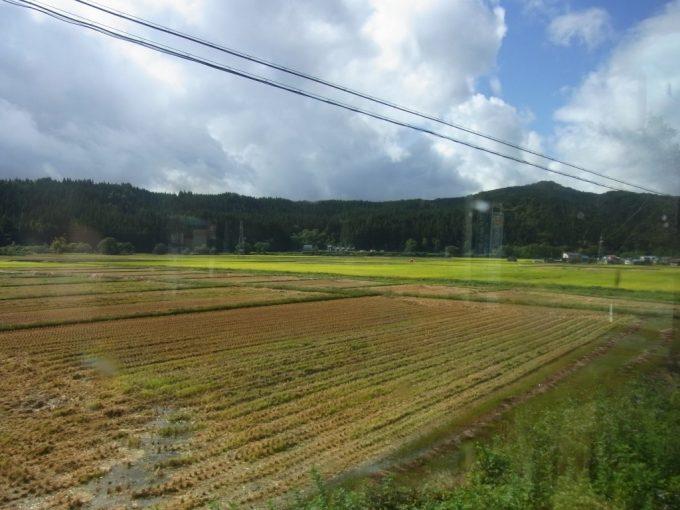 羽後交通バス車窓に広がる刈取り後の田んぼ