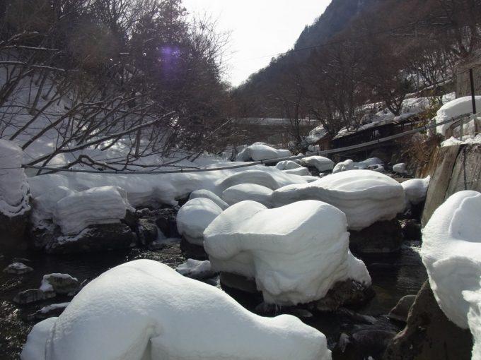 川原の岩にこんもりと積もる雪