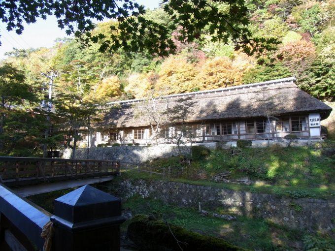 大沢温泉曲り橋から眺める茅葺の菊水館と秋の紅葉