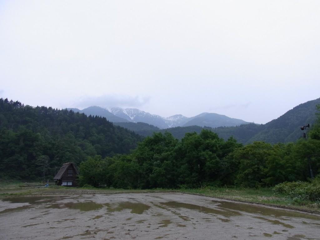暮れ始めの白川郷初夏の残雪の山