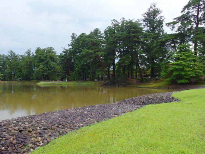 雨上がり夏の毛越寺大泉ヶ池芝生と玉石の美しい対比