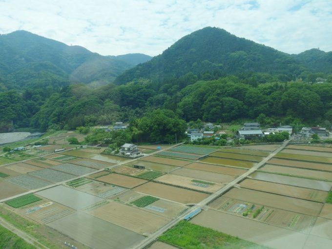 中央本線車窓に広がる初夏の山梨水を張ったばかりの田んぼ