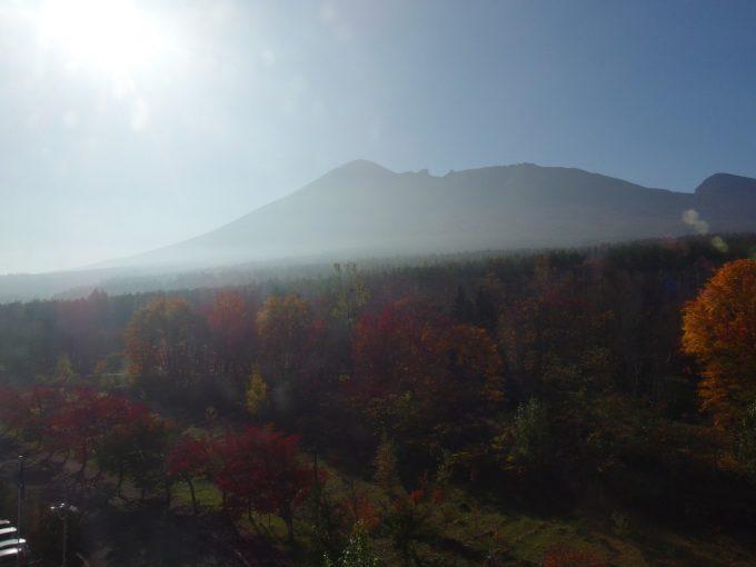 晴れつつある朝霧と紅葉に包まれる岩手山