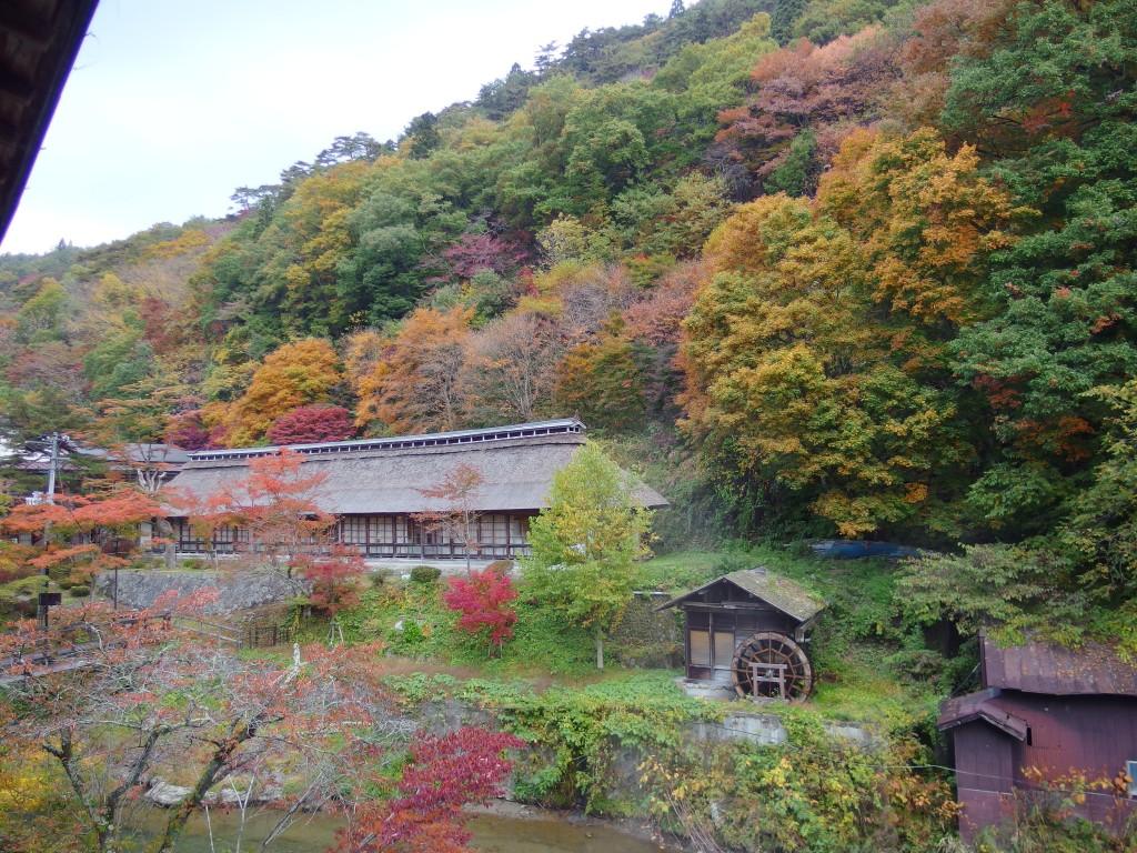 大沢温泉湯治屋自炊部中舘客室から眺める紅葉と菊水館茅葺屋根