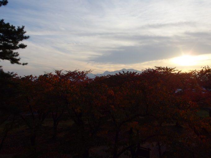 秋の盛岡夕方の岩手公園桜紅葉越しに眺める夕陽と岩手の山々