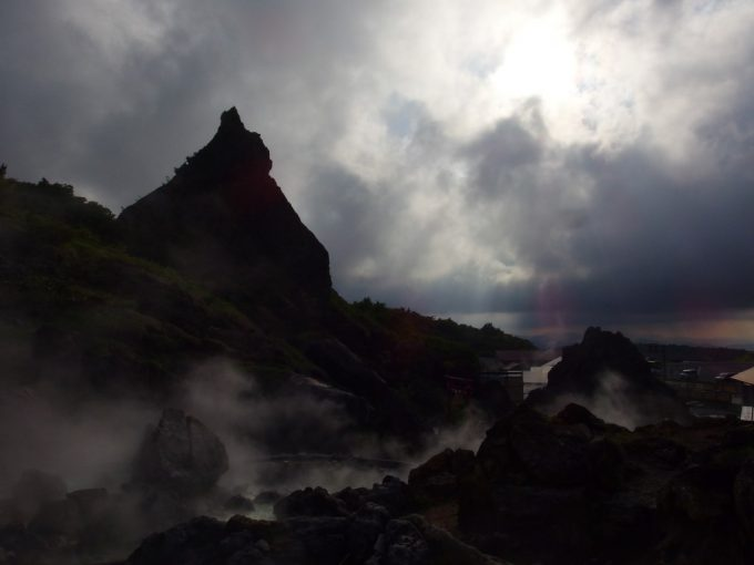 雲間から射す陽射しに照らされ神々しさすら感じさせる須川高原温泉のシンボル大日岩