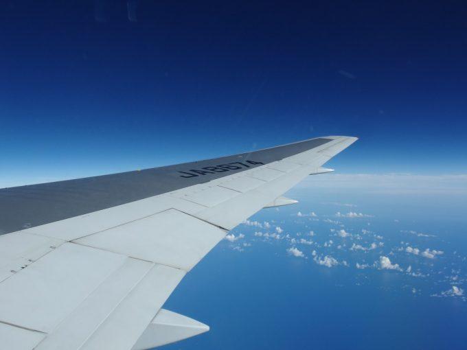 飛行機の窓の外には成層圏を感じさせる青さの空が広がる