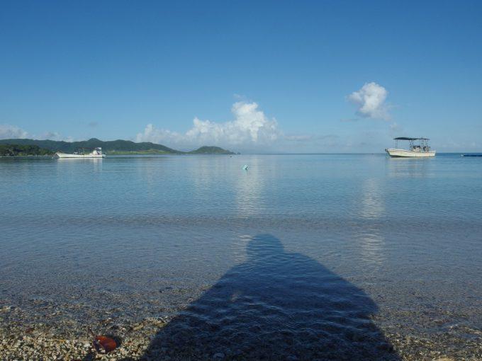 朝日に照らされ底地ビーチの海に落ちる自分の影