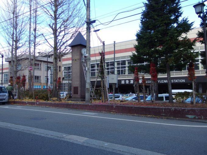 秋の終わり、紅葉の木を雪囲いする越後湯沢駅前