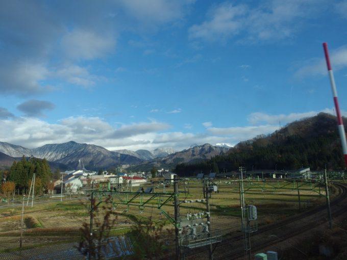 南越後観光バス車窓に広がる晩秋の田んぼと雪化粧の谷川連峰
