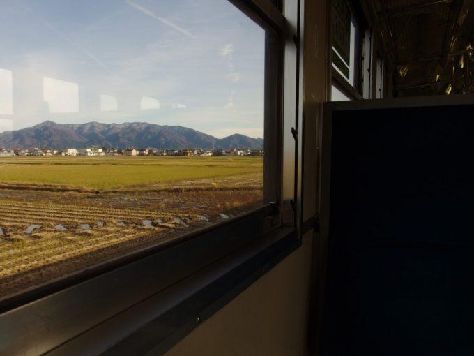 磐越西線キハ47車窓を彩る刈り終えた田んぼと雪化粧の山