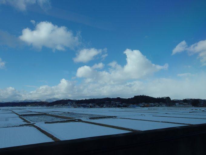 東北新幹線車窓に広がる雪景色と冬晴れの空