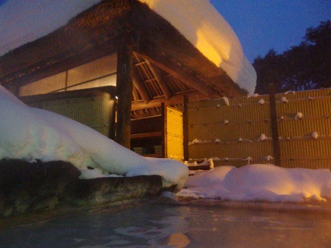 冬の旅館玉子湯天渓の湯から望む雪をかぶった茅葺屋根
