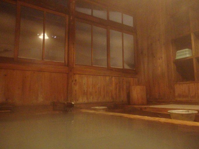 明治時代の茅葺屋根玉子湯に浸かりながら眺める窓の雪