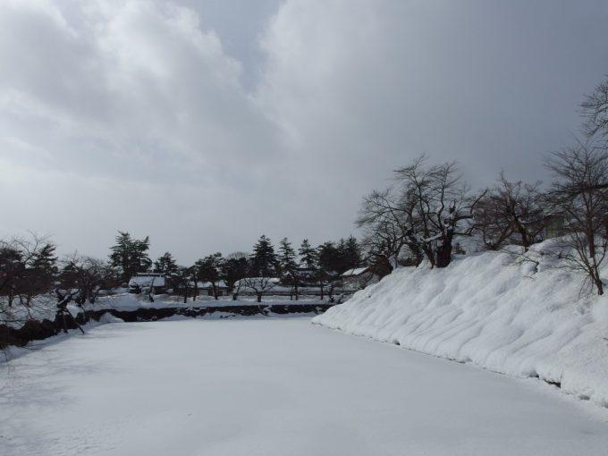 冬の米沢城跡凍てつき雪に埋もれたお堀
