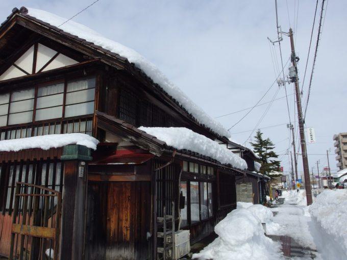 冬の米沢古い木造民家と歩道を埋める雪