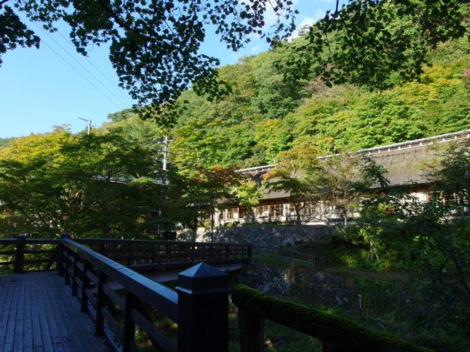 秋の昼下がり曲り橋から眺める大沢温泉菊水館の茅葺屋根