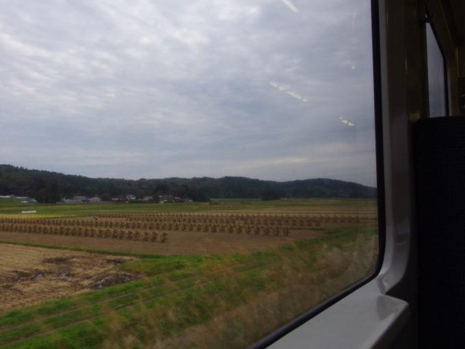 陸羽東線キハ110車窓から眺める刈り取られた田んぼ