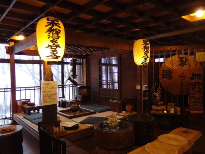 栃尾又温泉自在館ロビーで旅人を出迎える囲炉裏と秘湯を守る会提灯