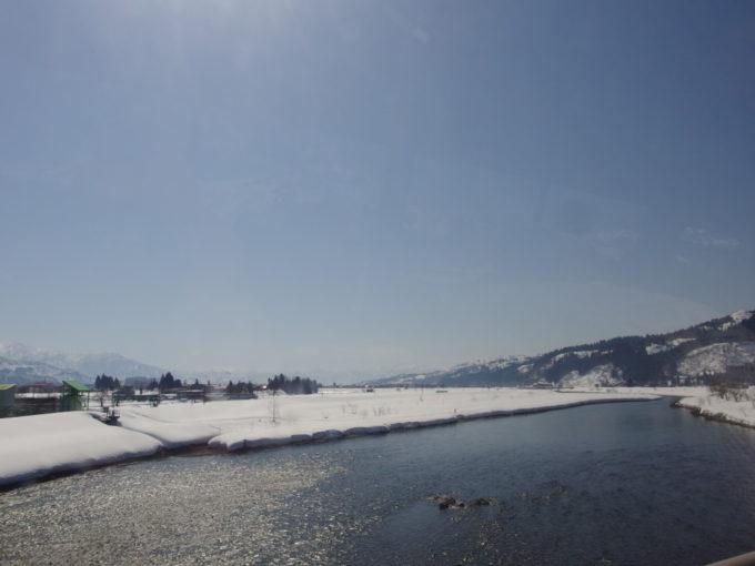雪解けの陽射しに照らされさらさらと流れる魚野川