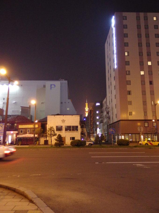 夜の札幌ビルの隙間から見え隠れするさっぽろテレビ塔