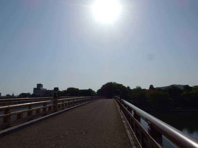 朝日に照らされた鶴見橋を渡り日本三名園後楽園へ
