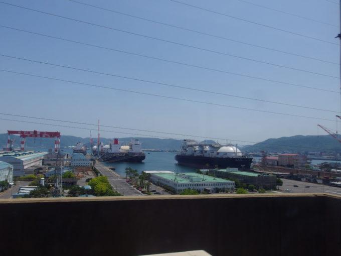 本四備讃線瀬戸大橋線列車はいよいよ四国本島に上陸し川崎重工の造船所を眺める