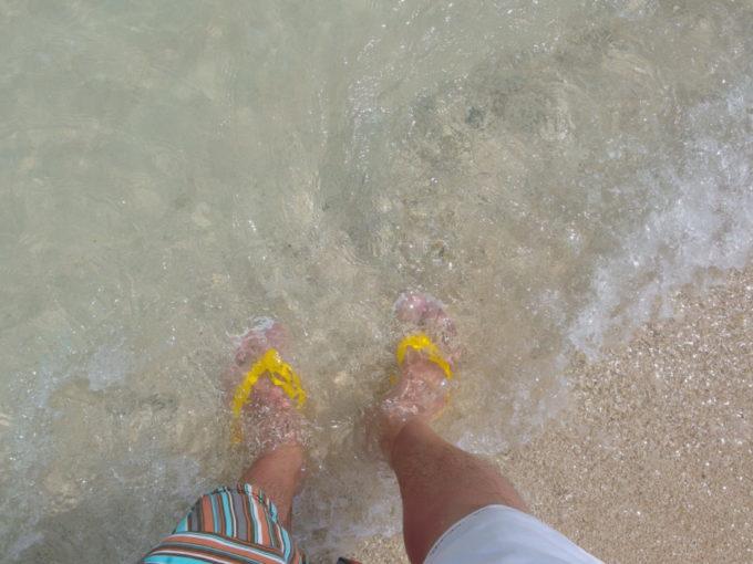 足に感じる竹富島コンドイビーチの透明な波の鼓動
