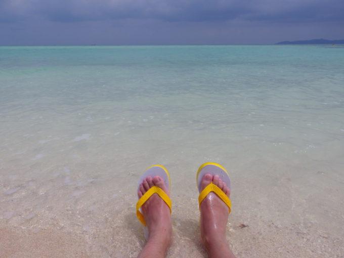 夏の竹富島コンドイビーチ波打ち際に座り海の鼓動を感じる