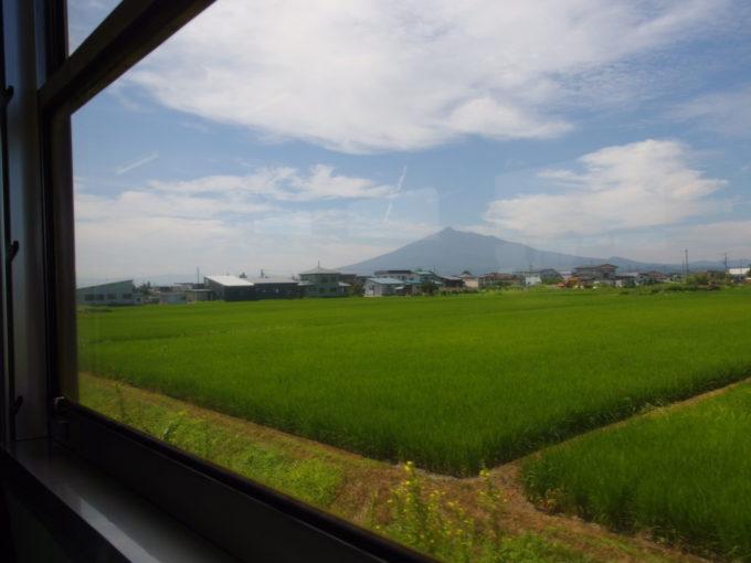 JR五能線キハ48車窓から眺める青い田んぼと津軽富士岩木山