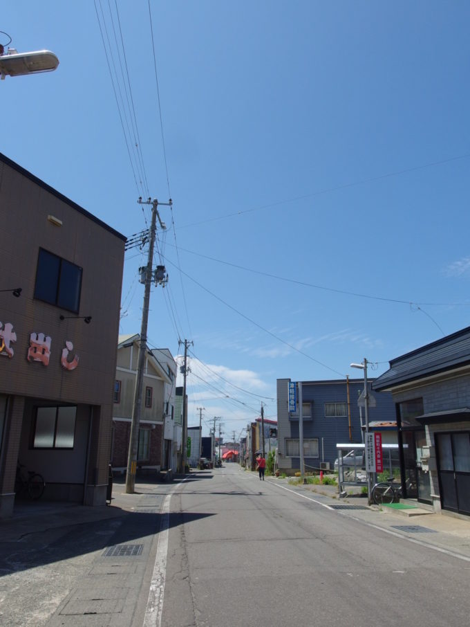 夏空の下歩く金木の町