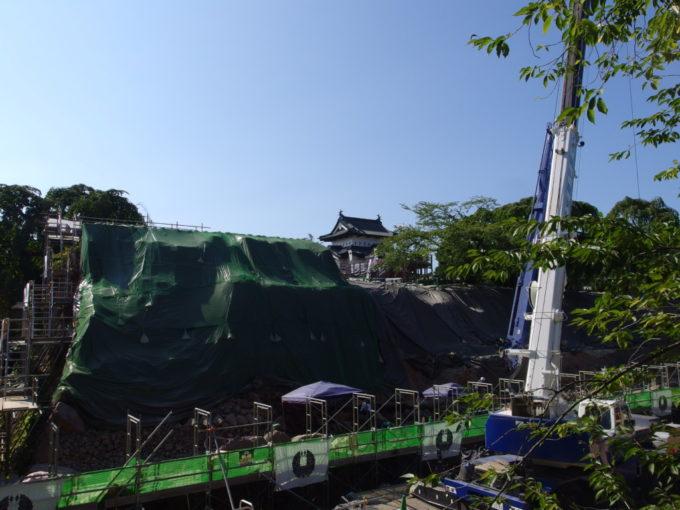 夏の弘前公園改修工事中の石垣と遠くに隠れる弘前城天守閣
