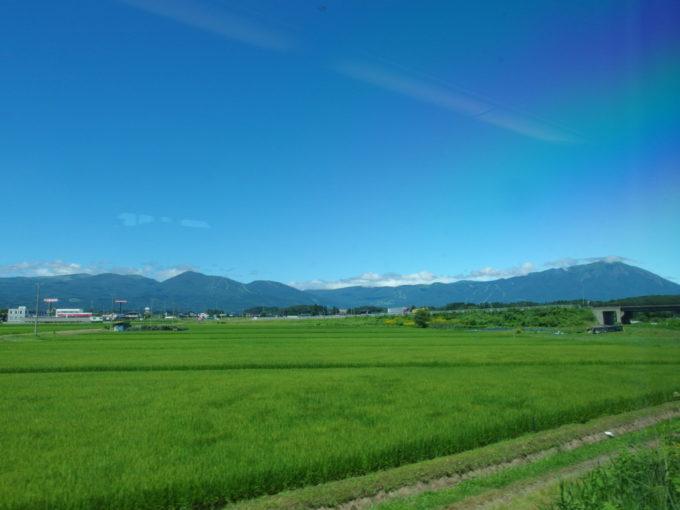 E6系こまち号東京行き車窓に広がる夏晴れの岩手の田園と岩手山