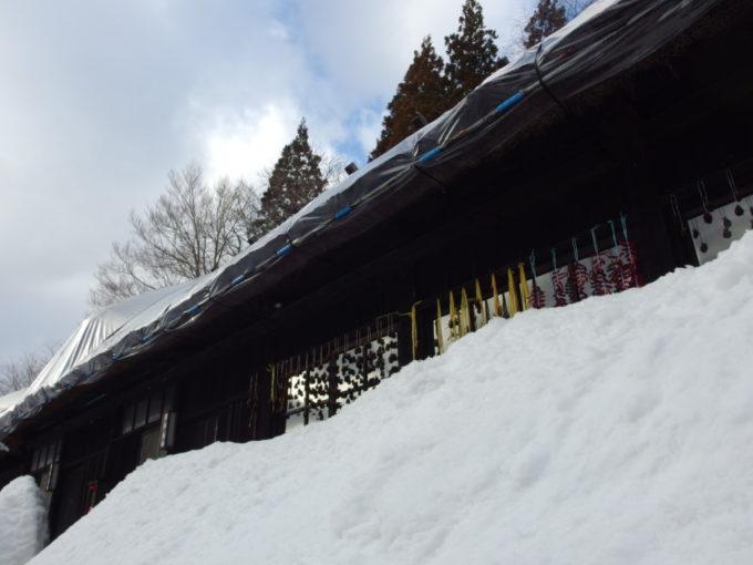 冬の乳頭温泉郷鶴の湯軒下に吊るされた干し柿や鷹の爪